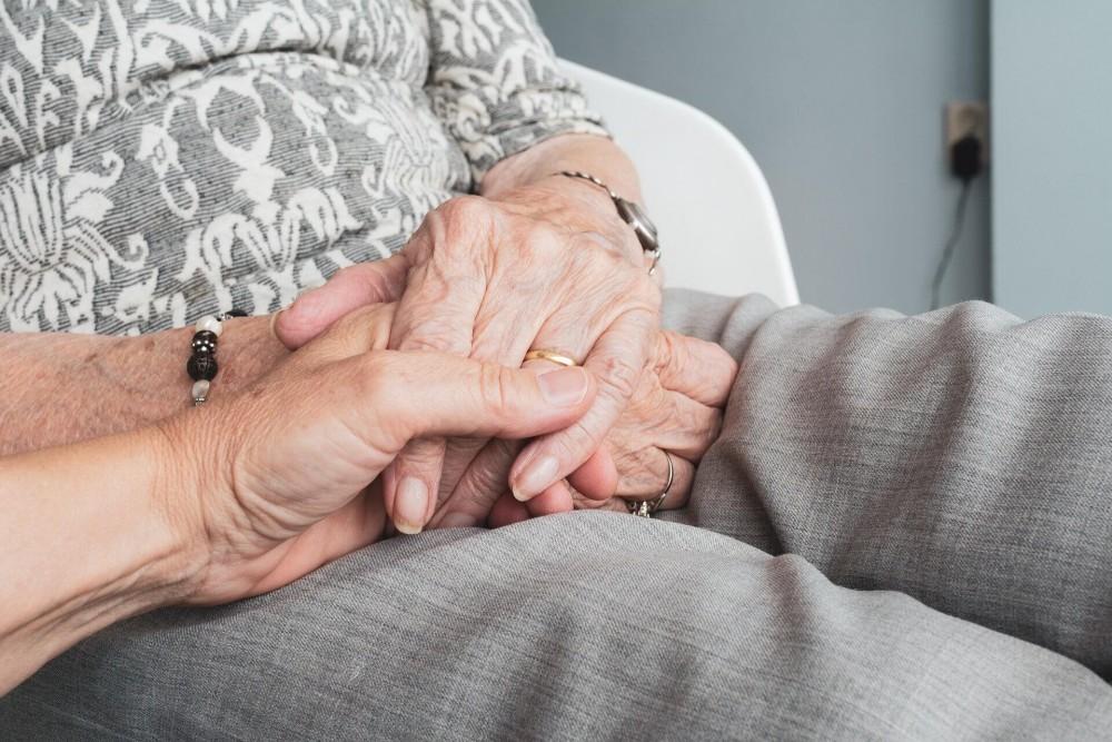 opiekunka trzymająca podopieczną za rękę